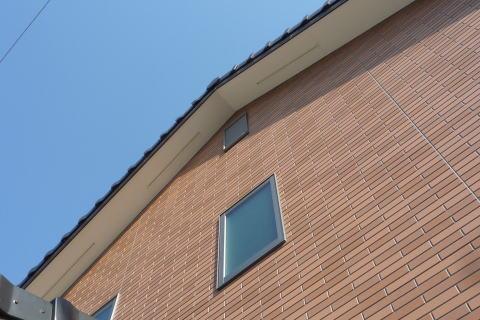 オーソドックスな切妻屋根にタイル調サイディング張りが施された住宅