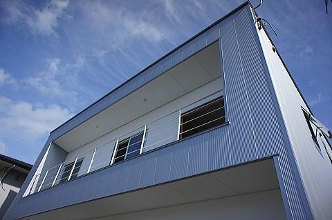 シャープな金属板が純白の塗り壁を取り囲む住宅