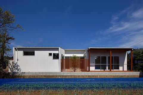 白い金属壁を外壁に張った平屋住宅